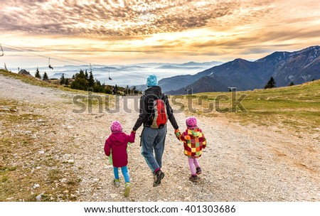 Family hiking in the mountains on ski slope into sunset. Mother and two twin children are hiking on the foot path in the nature in alps and hills. Active family . - stock photo