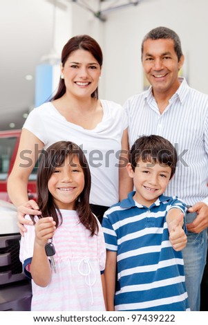 Family holding the keys of a new car - stock photo