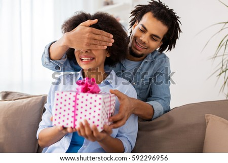 family, holidays and people concept - happy couple with gift box at home