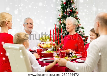 family, holidays, generation, christmas and people concept - smiling family having dinner and praying at home - stock photo