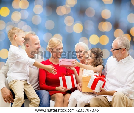 family, holidays, generation, christmas and people concept - smiling family with gift boxes sitting on couch over blue lights background - stock photo