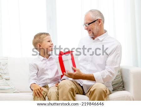 family, holidays, generation, christmas and people concept - smiling grandfather and grandson with gift box sitting on couch at home - stock photo
