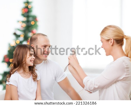 family, holidays, technology and people - smiling mother, father and little girl with camera over living room and christmas tree background