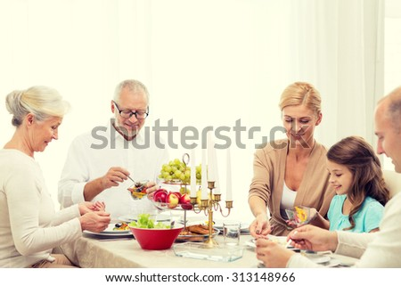 family, holidays, thanksgiving, thanksgiving, generation and people concept - smiling family having dinner at home - stock photo