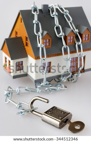 family house and metallic chain as a protection - key lock security system  - stock photo