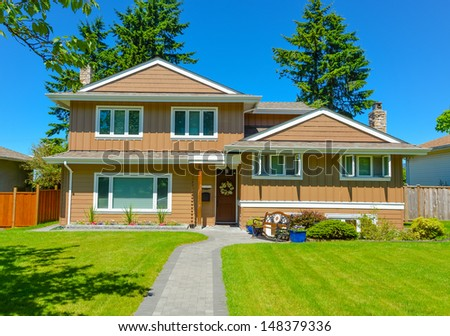 Family house in suburban area of Vancouver, Canada. North American house on blue sky background on a sunny day.
