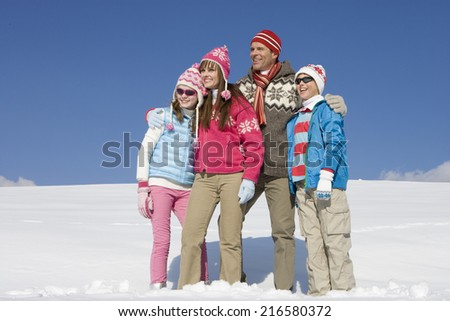 Family hugging and standing in snow