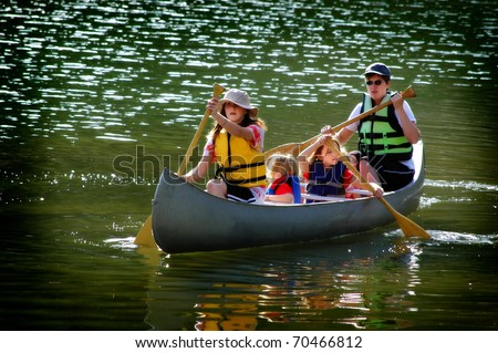 Family in a canoe on a lake in the summer - stock photo