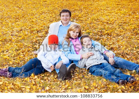 Family in autumn park. Mother, fatherr and children outdoors