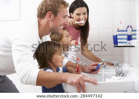 Family In Bathroom Brushing Teeth - stock photo