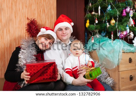 Family in christmas hats near spruce at home - stock photo
