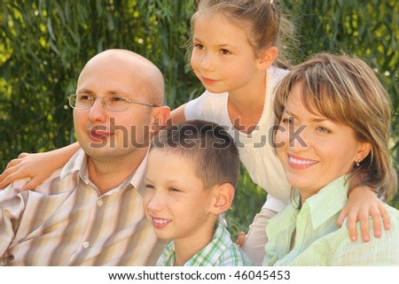 family in early fall park. dad, mom and little boy sitting at the grass. little girl is standing behind their. all of them is looking away - stock photo