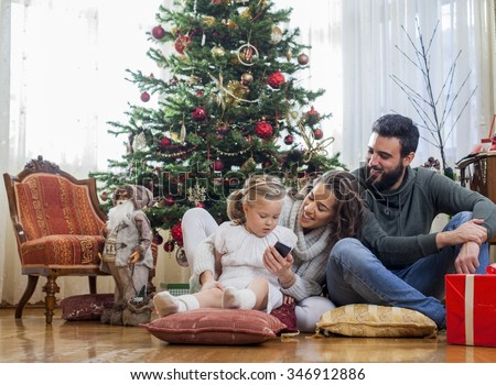 Family in front of Christmas tree, opening presents  - stock photo