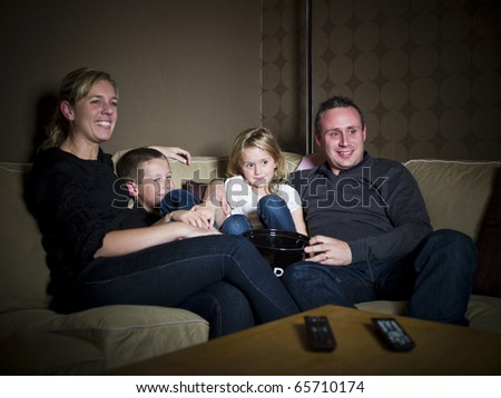 Family in front of The Television sitting in the sofa - stock photo