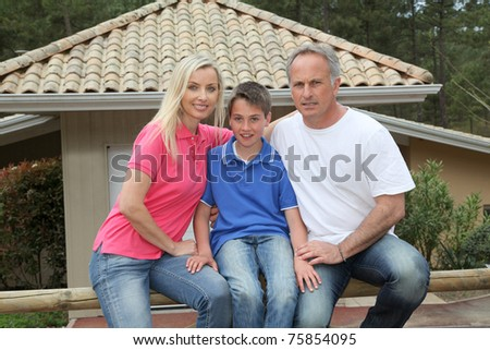 Family in front of their house - stock photo