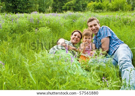 Family in green grass - stock photo