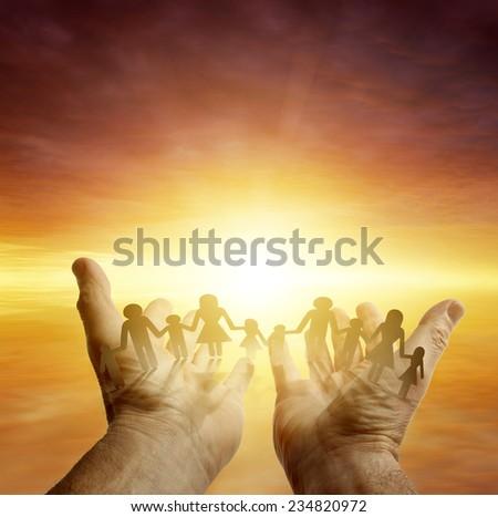 Family in hands. Bright sky - stock photo