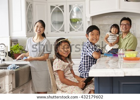 Family In Kitchen Doing Chores And Using Digital Devices