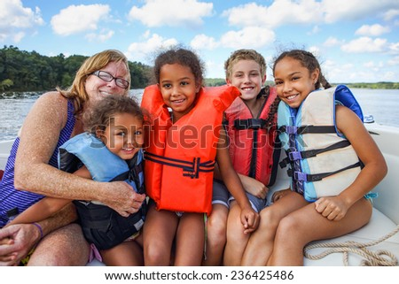 Family in Life jackets on a boat on a lake - stock photo