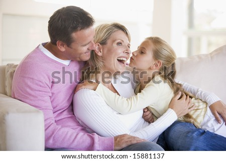 Family in living room with young girl kissing woman - stock photo