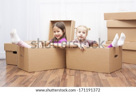 family in move, smile sisters in the box - stock photo