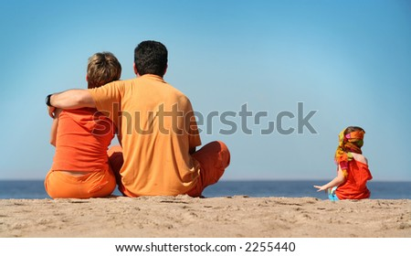 Family in orange clothes on the beach - stock photo