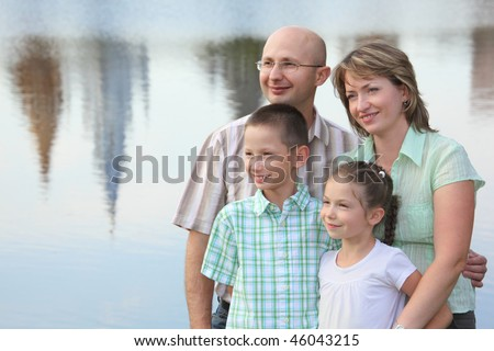 family in park. father, mother, little girl and little boy on pond background. man is embracing his wife - stock photo