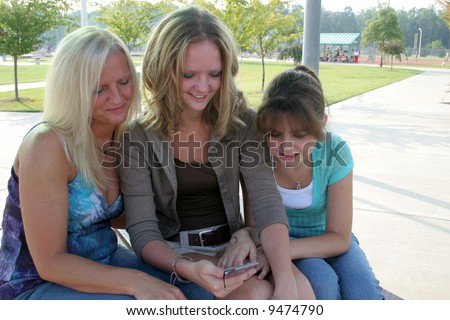 Family in park looking at the cell phone