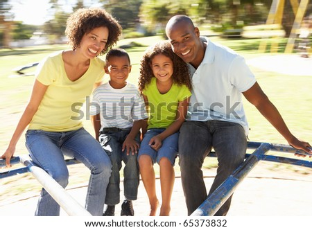 Family In Park Riding On Roundabout - stock photo