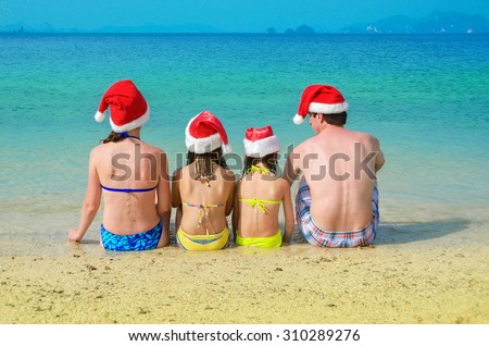 Family in santa hats having fun on beach vacation, new year and christmas holiday concept  - stock photo