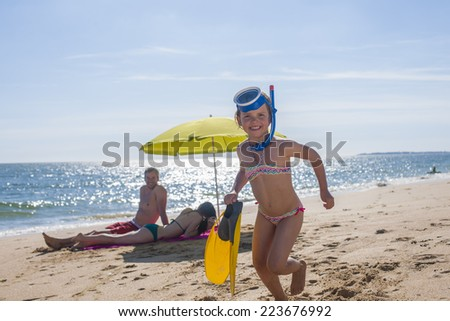 Family in swimwear on the beach Mom and Dad sitting under an umbrella and the little girl with a mask and fins running towards the camera - stock photo