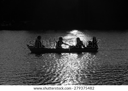 Family in the boat on the lake in sunset glow. Silhouettes. Harmony with nature idea.  Aged photo. Black and white. - stock photo