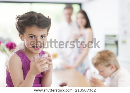 family in the kitchen at breakfast a little girl at foreground - stock photo
