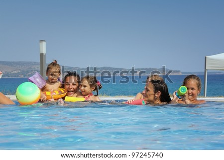Family in the pool by the sea - stock photo