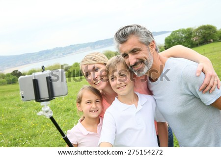 Family in vacation taking selfie picture with smartphone - stock photo