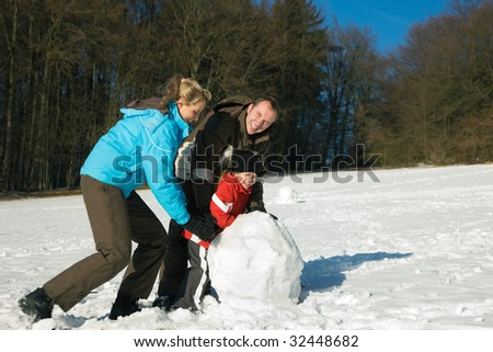 Family in wintertime attempting to build a snowman - stock photo