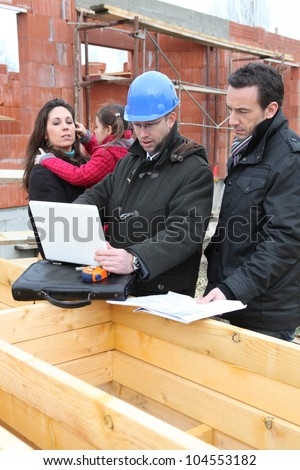 Family inspecting there unfinished future home - stock photo