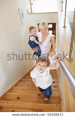 Family is on the staircase looking in the camera - stock photo