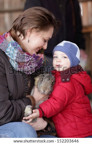 Family is posing with rabbit on a farm - stock photo