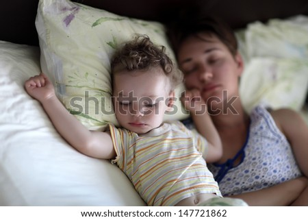 Family is sleeping on a bed at home in the morning - stock photo