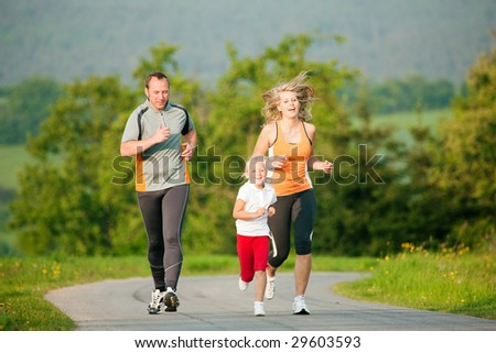 Family jogging outdoors with the kid - stock photo