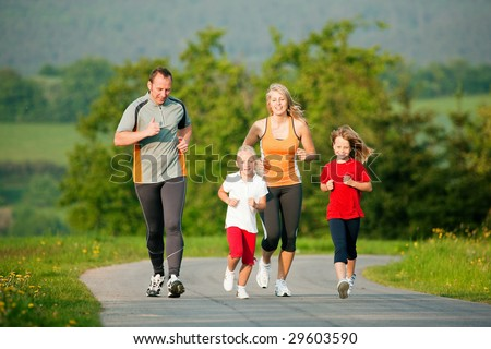 Family jogging outdoors with the kids - stock photo