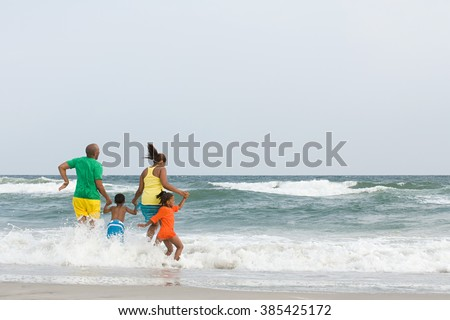 Family jumping in the sea - stock photo