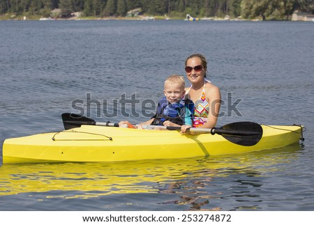 Family Kayaking together on a beautiful lake - stock photo