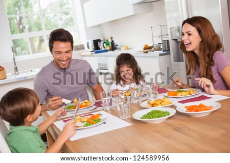 Family laughing around a good meal in kitchen - stock photo