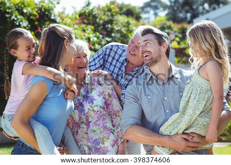 Family laughing in back yard during sunny day - stock photo