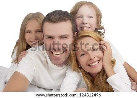 family laughing together while laying on bed covered with white linen isolated over white background - stock photo