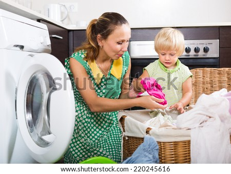 Family laundry. Happy woman with child putting clothes in to washing machine at home  - stock photo