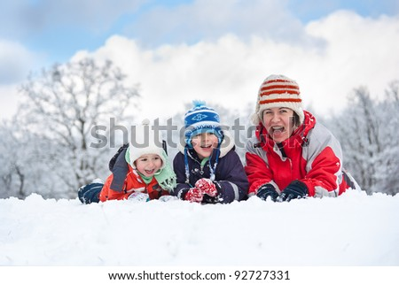 Family laying down in the snow - stock photo