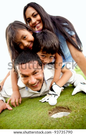 Family laying on the golf course next to the whole